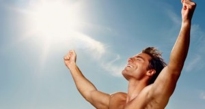 Portrait of an excited young man with hands raised towards the sky
